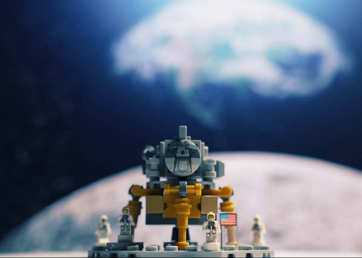 Lego model of a rover with the moon and the Earth in the background.