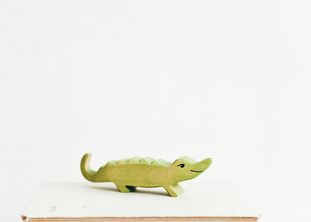 A small green wooden toy crocodile.