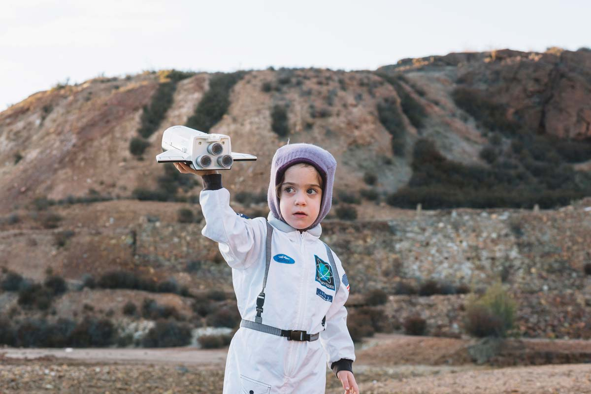 Little child dressed as an astronaut standing outside on rocky hills making their toy rocket fly.