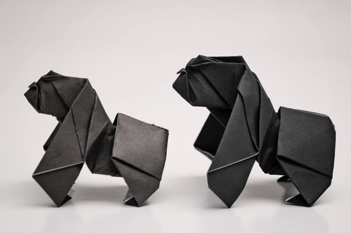 Two origami monkeys standing up side by side.