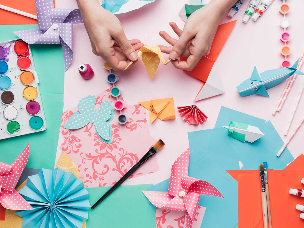 A bird's eye image of a craft table full of origami paper, models and equipment.