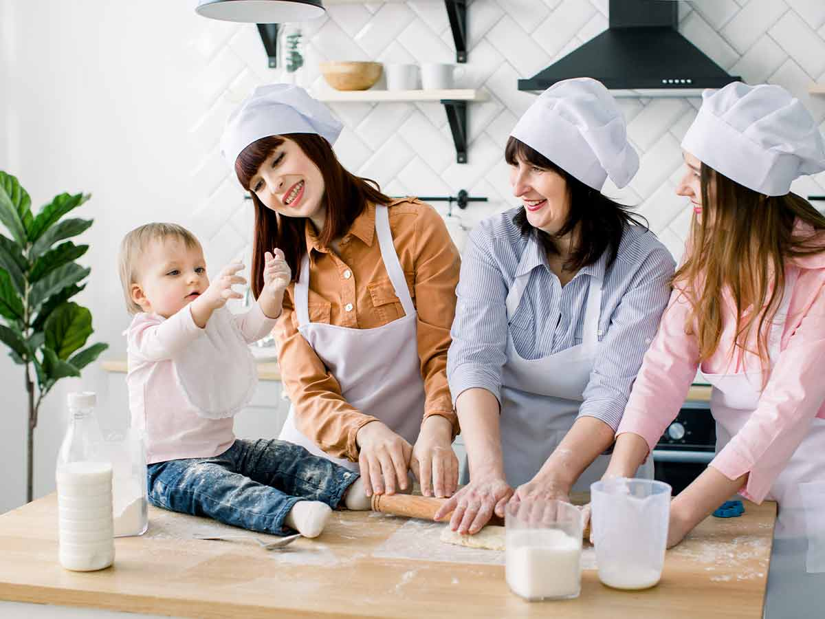 Three women in the kitchen baking a dragon birthday cake while a little toddler sits on the counter playing with ingredients.