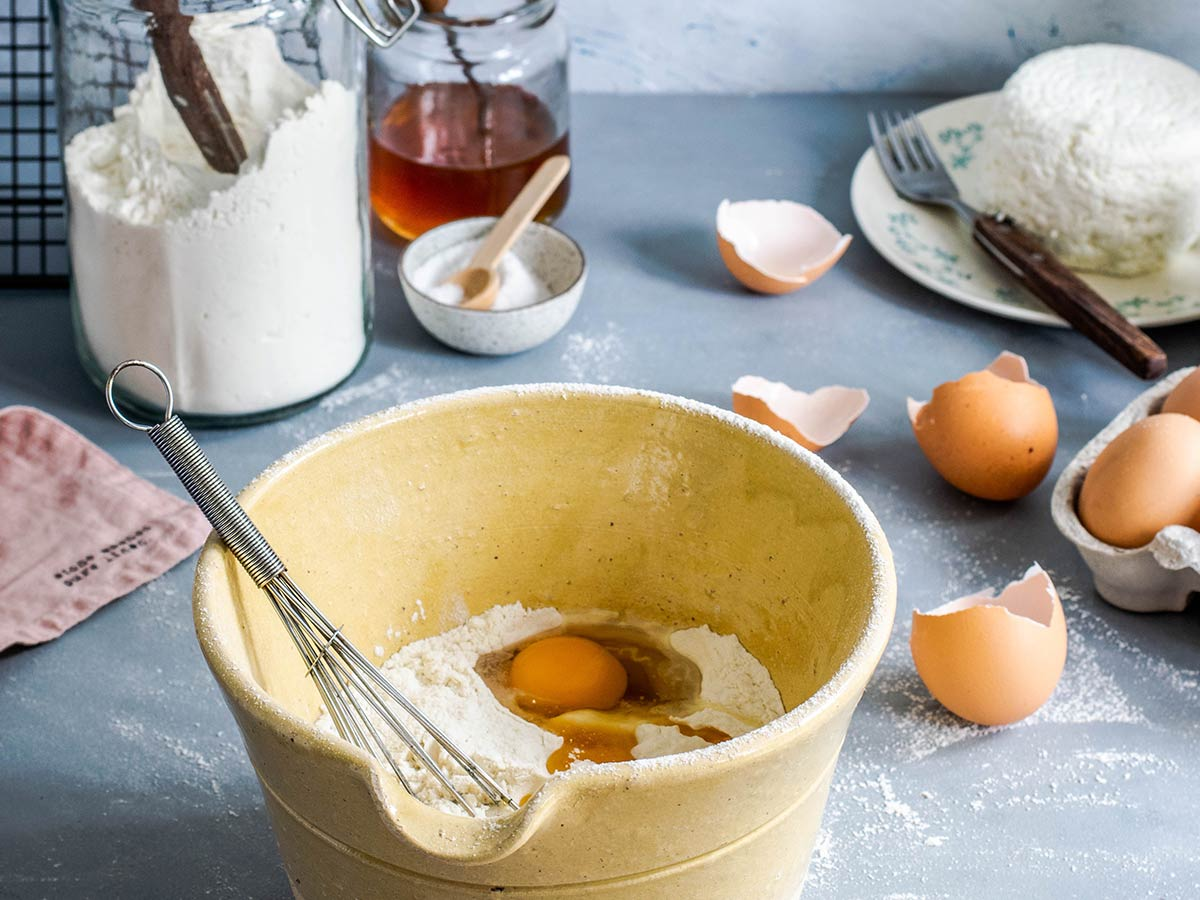 A bowl of flour and eggs with all the rest of the ingredients for making a dragon cake.