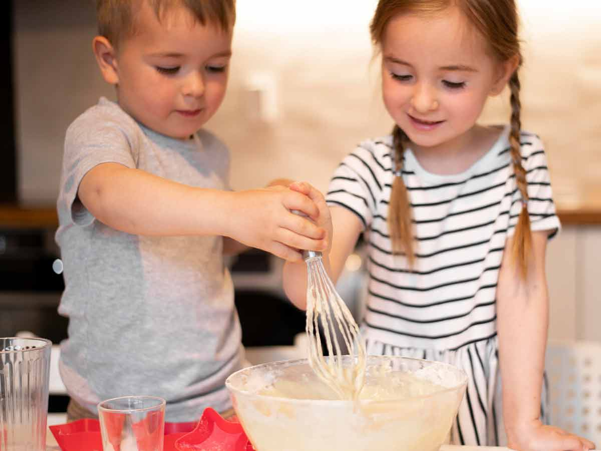 Little girl and boy in the kitchen making a dragon cake.