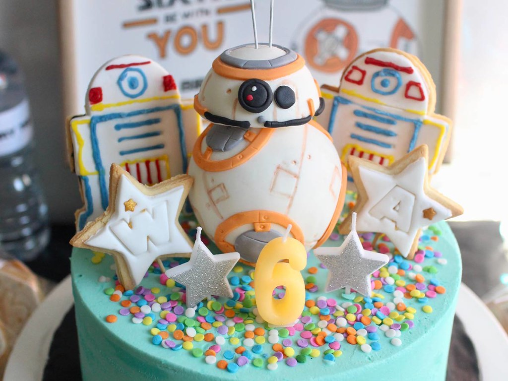 A colourful Star Wars birthday cake with a Star Wars cake topper on top.