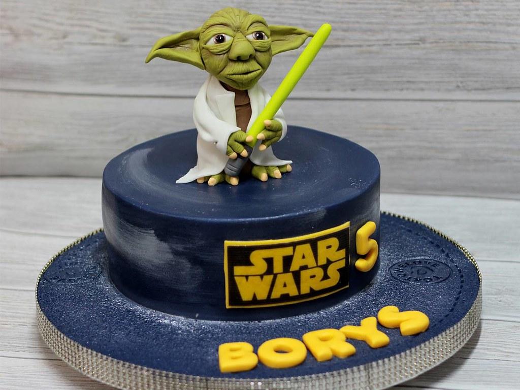 A Star Wars birthday cake with a Yoda cake topper.
