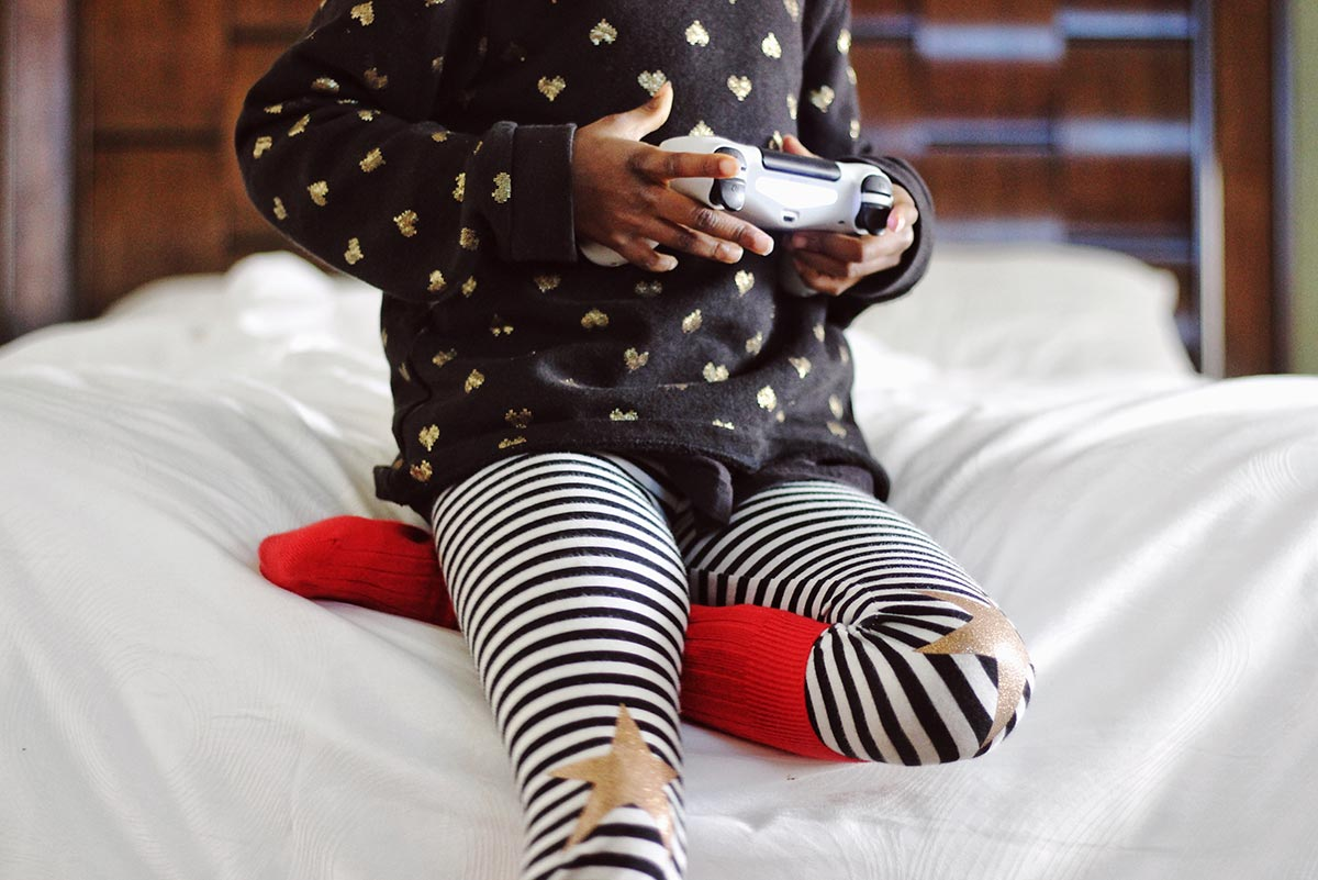 Close up of a child holding a games console controller, playing Fortnite.