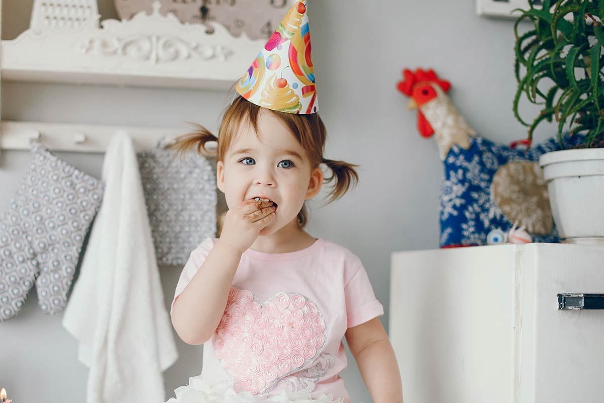 A little girl wearing a party hat eating a slice of Trolls cake.