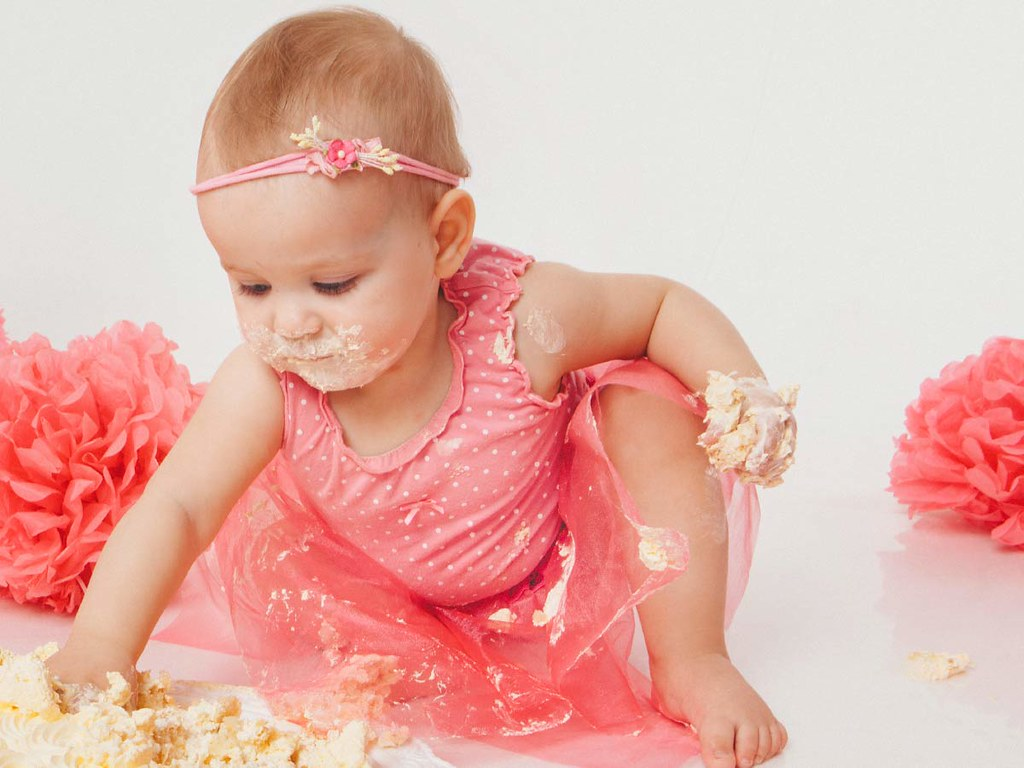 A little girl in a pink dress eating birthday cake.