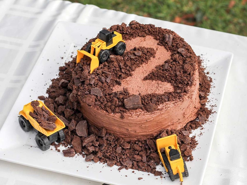 A chocolate birthday cake with toy tractors on top acting as tractor cake toppers.