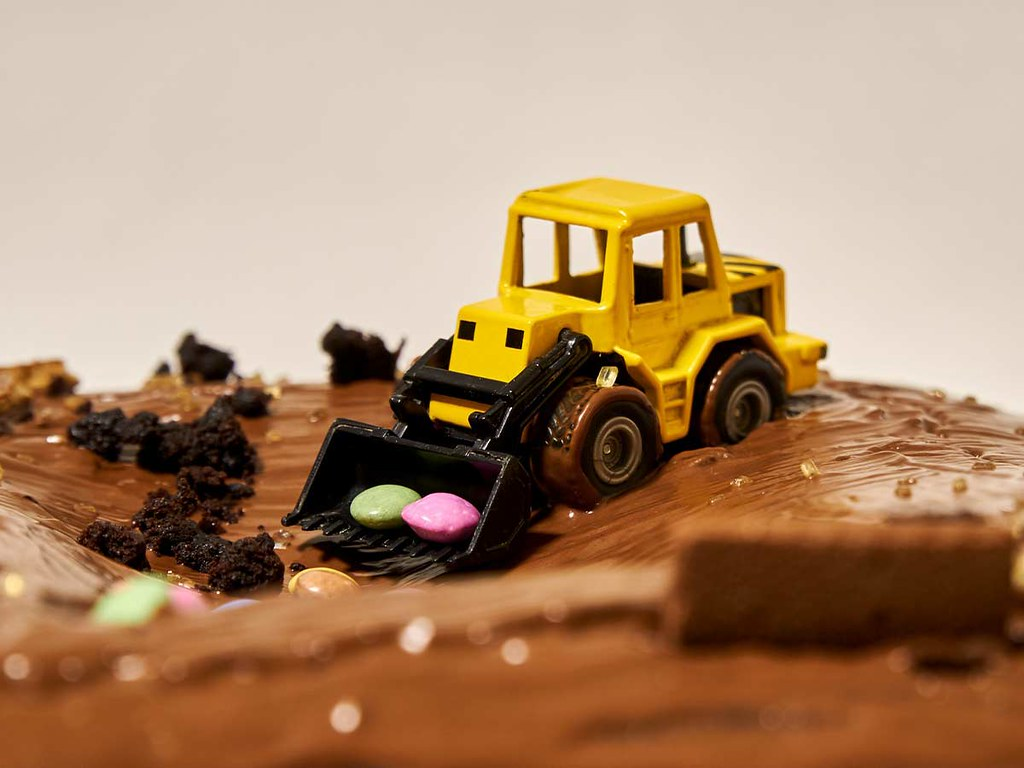 A close up image of a yellow tractor on top of a chocolate birthday cake.