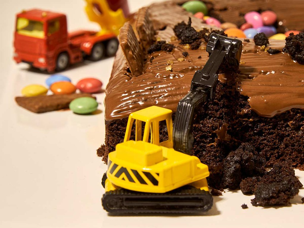 A close up image of a toy vehicle on a construction themed birthday cake.
