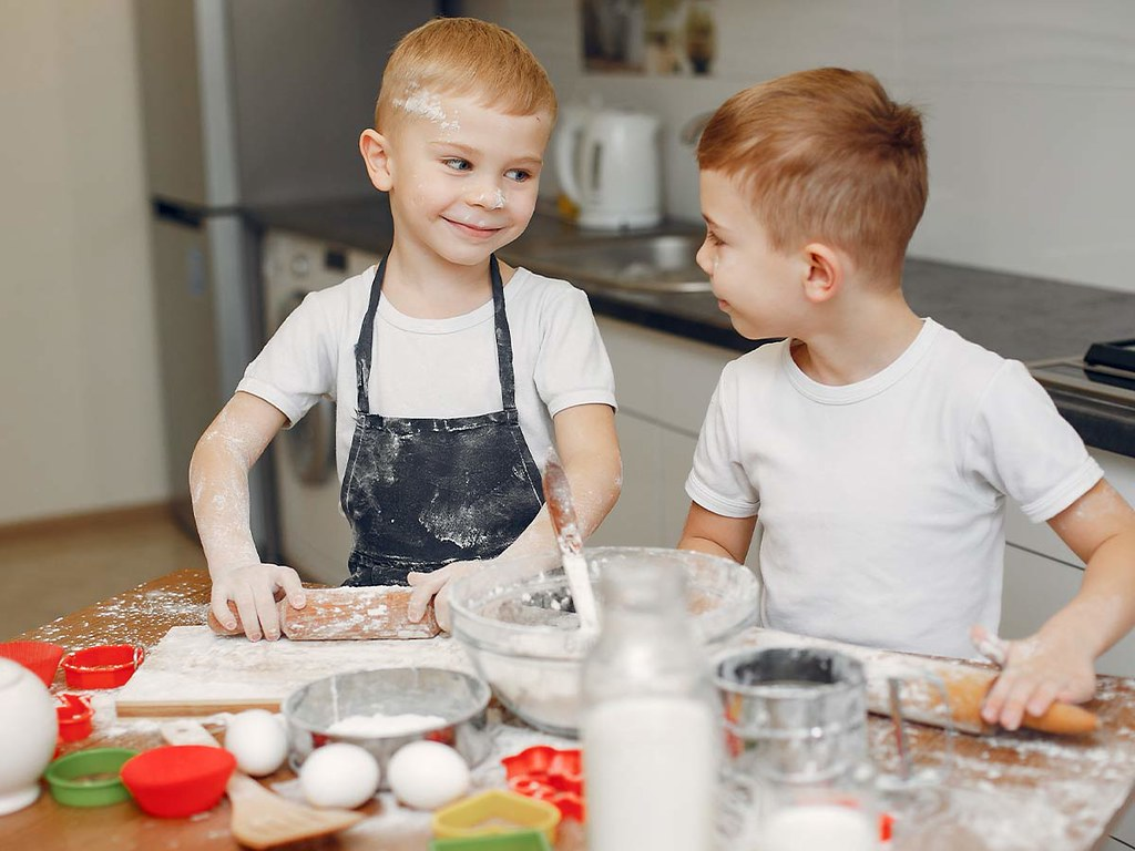 Two young boys smiling as they bake a Batman cake together.