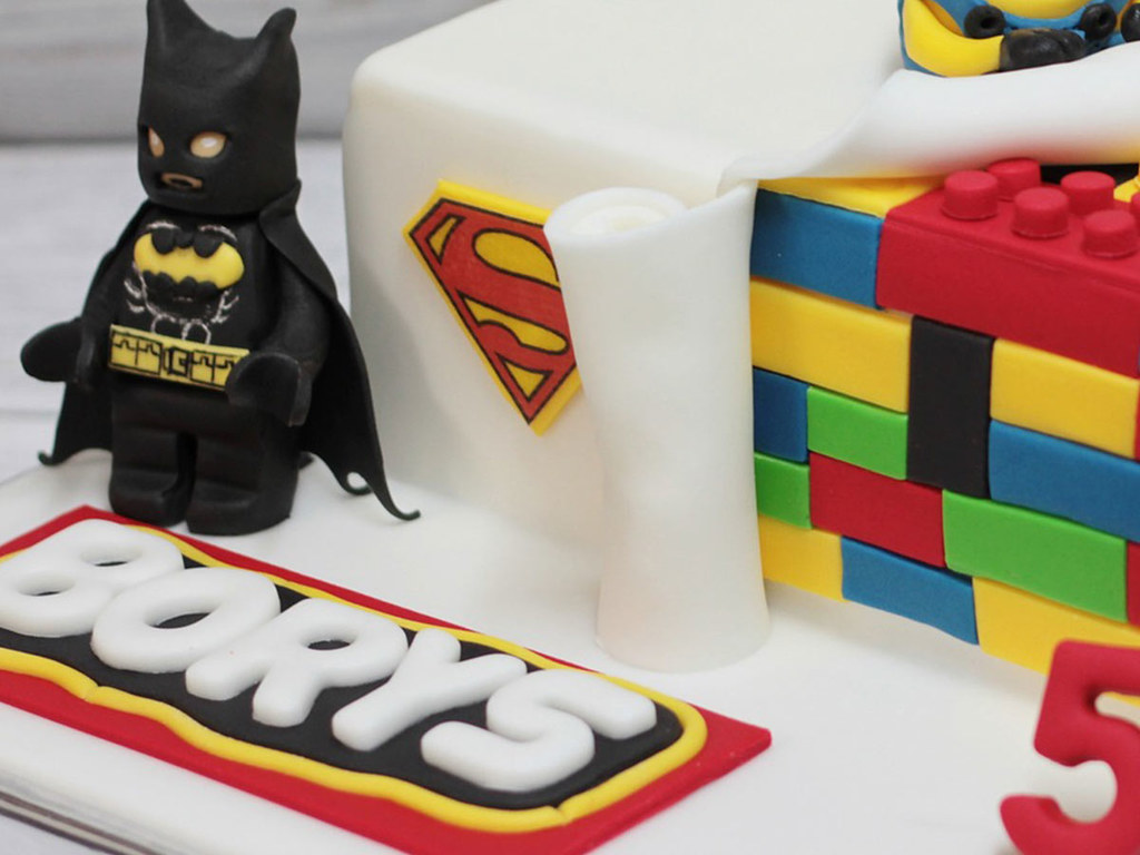 A close up image of a Batman figure next to a cake covered in fondant icing.