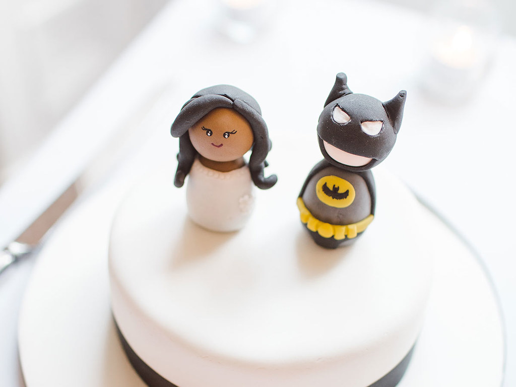 Two Batman cake toppers on top of a white cake.