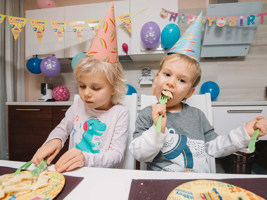 Two kids wearing party hats, enjoying a slice of cake at a birthday party.