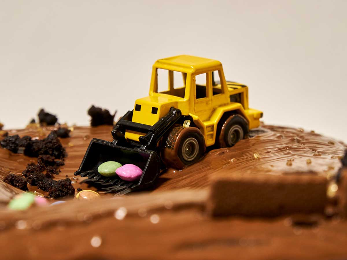 Chocolate cake with a yellow toy car digger on it shovelling sweeties.