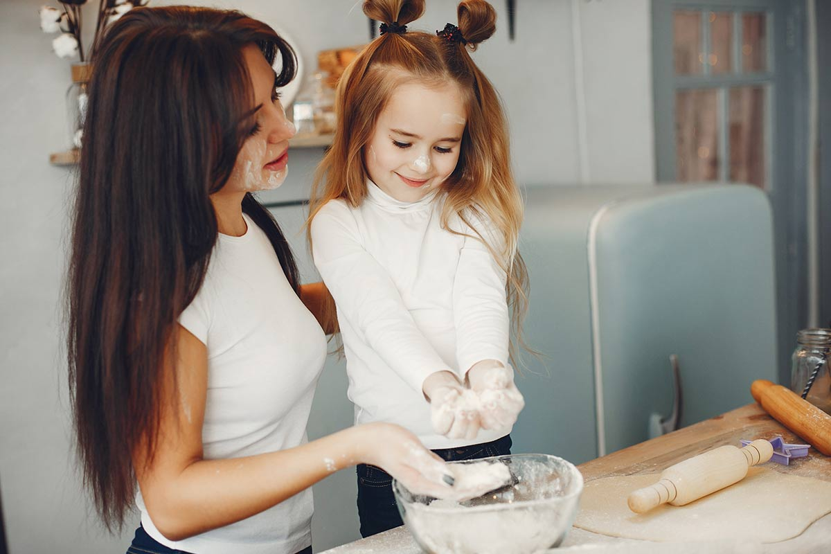 Mum and daughter in the kitchen baking a car cake together.