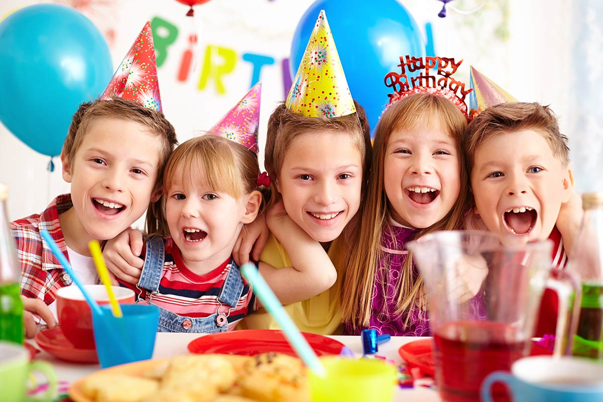 A group of kids smiling as they eat cake at a birthday party.