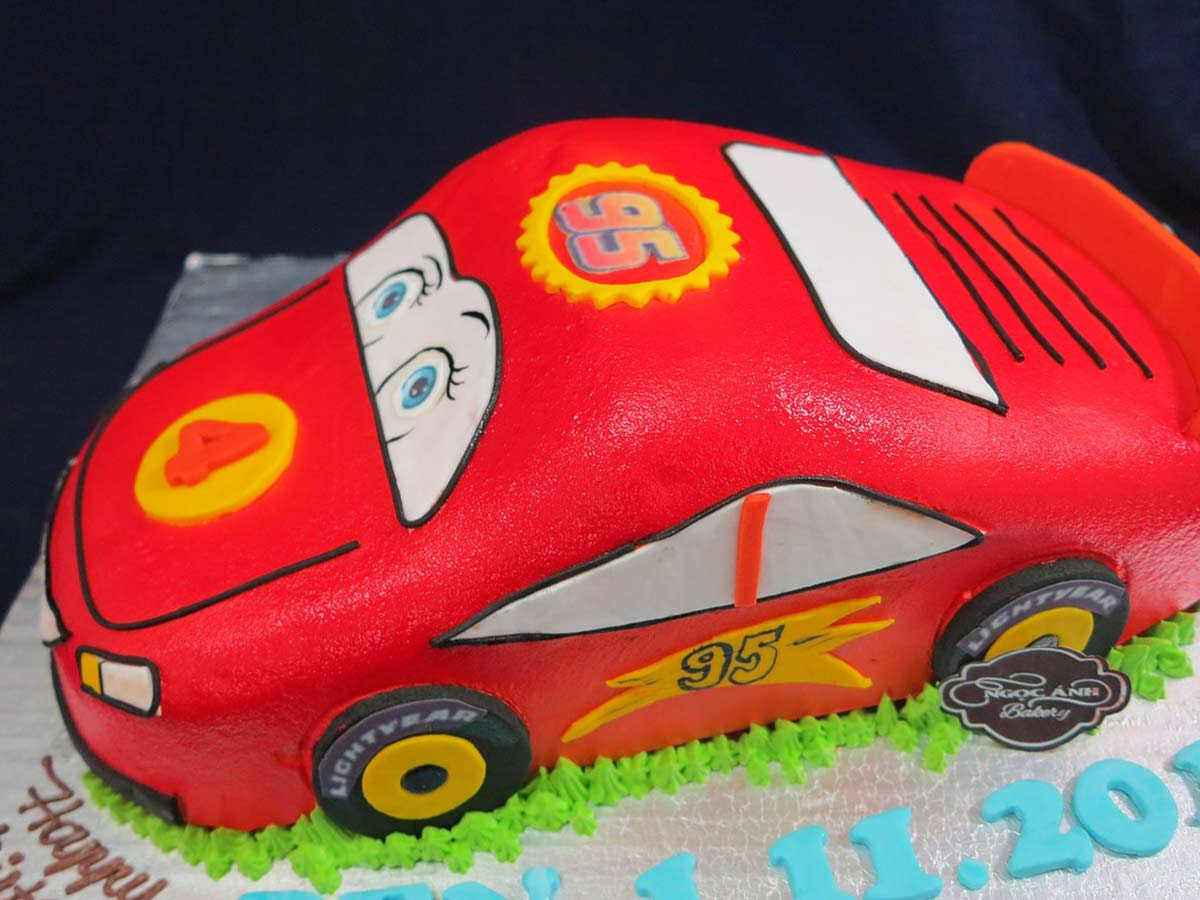 Red car cake that looks like Disney's 'Cars' character Lightning McQueen.