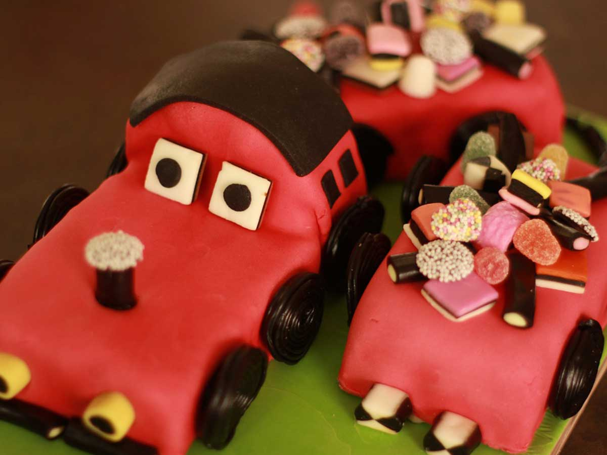 Cake in the shape of a red car with sweeties decorating it on top.
