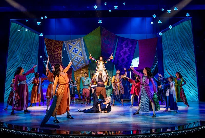 The cast of Joseph and the Amazing Technicolor Dreamcoat on stage pointing at the main character Joseph who is sitting on the shoulders of another actor.