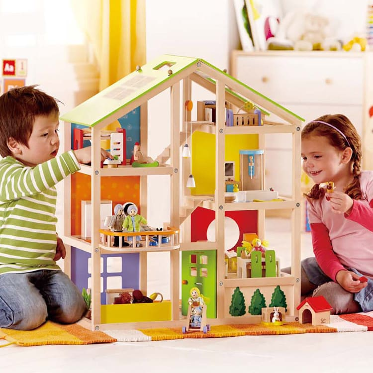 Little boy and girl playing with the Hape All Season House.
