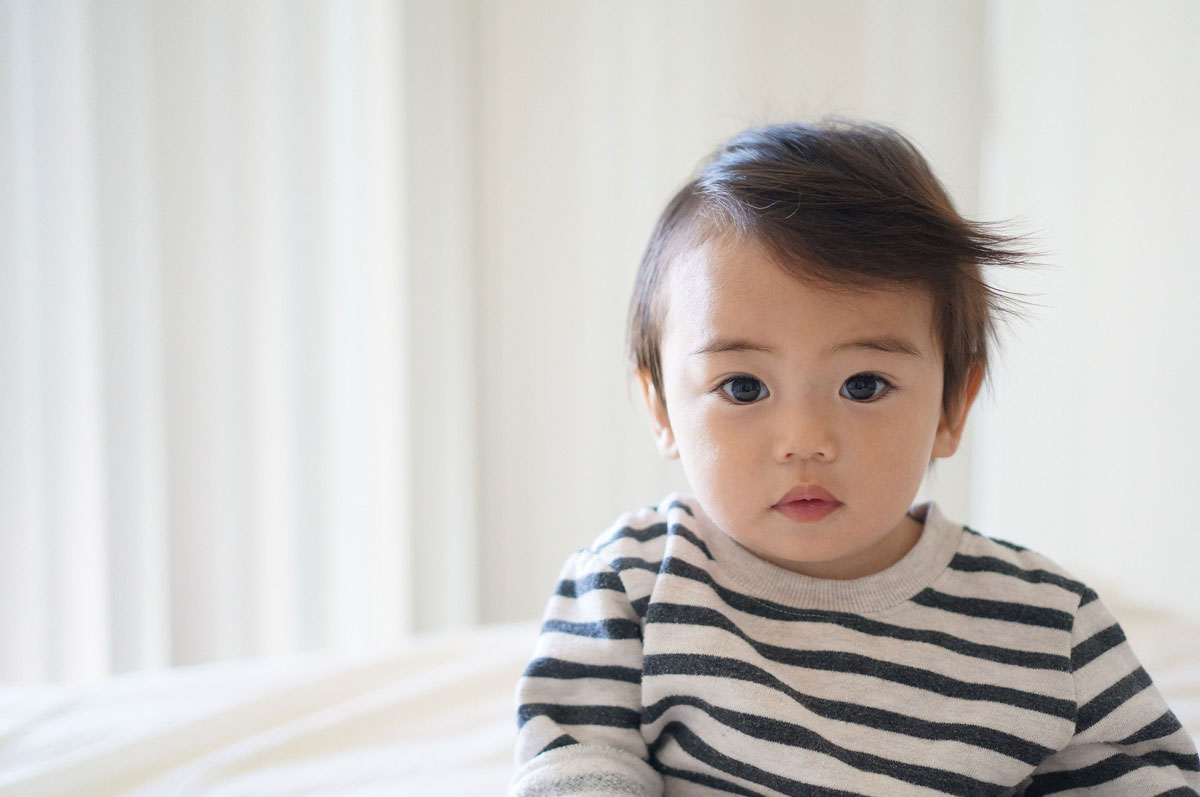 A baby wearing a navy and white striped tracksuit top looking into the camera.