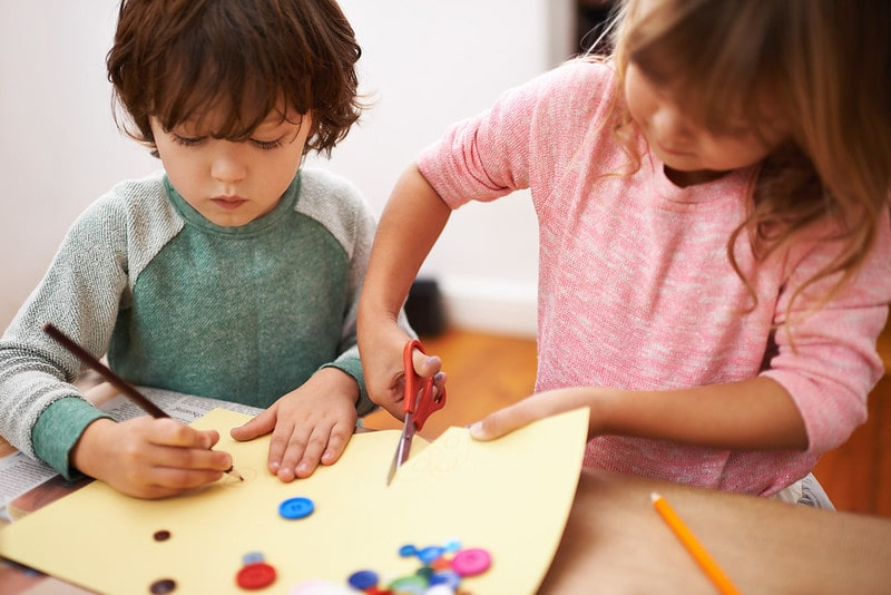 Young girl and boy sat at the table cutting paper and doing crafts at home.