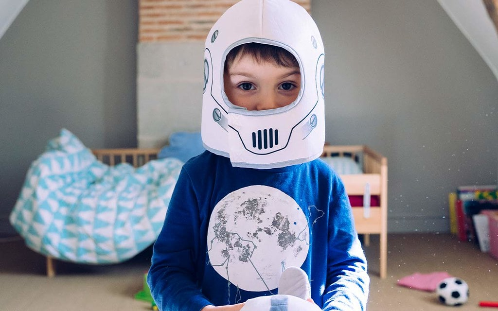 Boy wearing a homemade Star Wars Stormtrooper helmet.