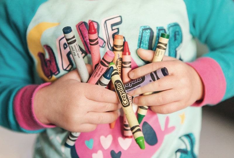 Close up of a preschooler child holding Crayola crayons.