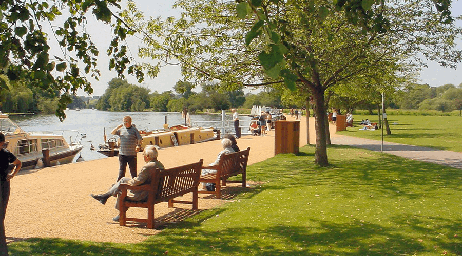 People sitting on benches by the River Thames at Higginson Park.