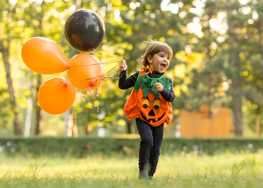 A child dressed in a Halloween costume holding orange and black balloons.
