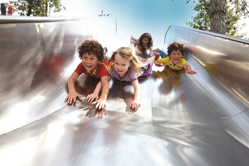 Children enjoying sliding down a slide head-first at Queen Elizabeth Olympic Park.