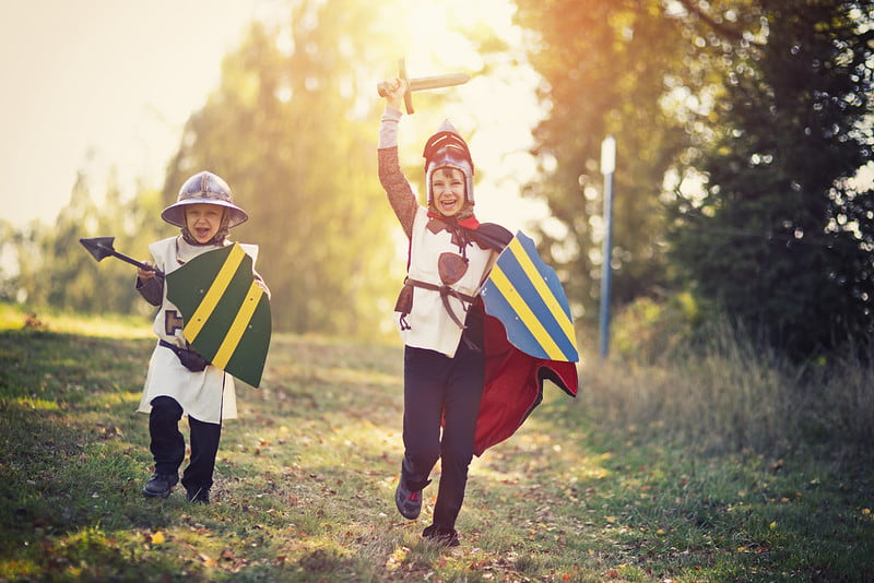 Kids dressed as knights running through the outdoors with shields.