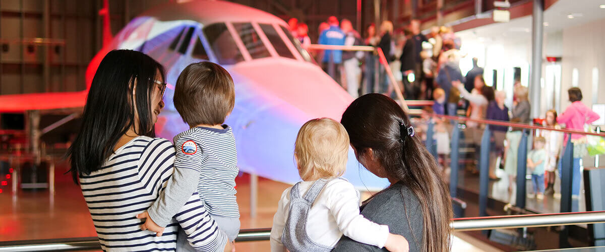 Two mothers holding their toddlers and looking at a Concorde.