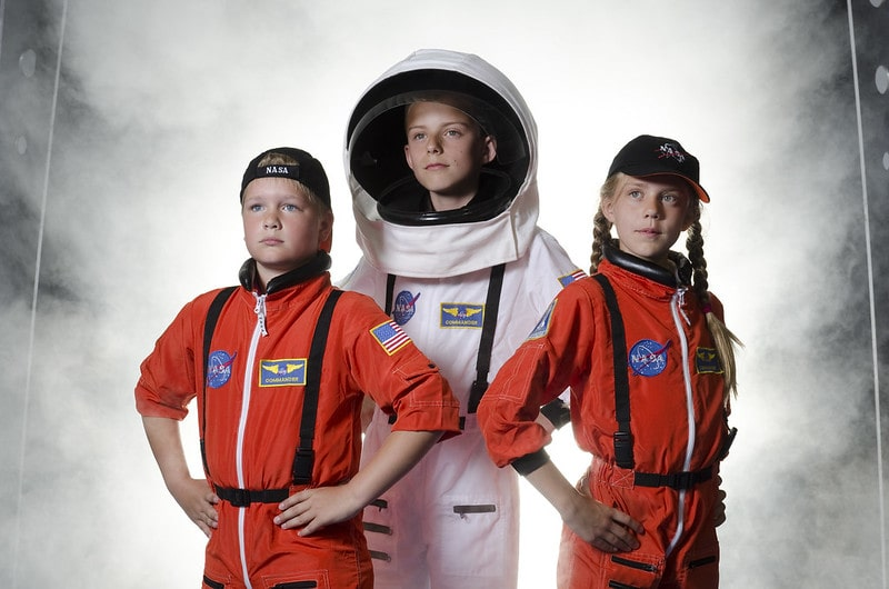 Three kids dressed as astronauts on a visit to the National Space Centre in Leicester.