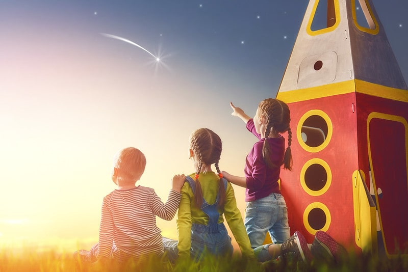 Three kids playing with a large toy rocket, gazing up at the amazing night sky looking at stars.