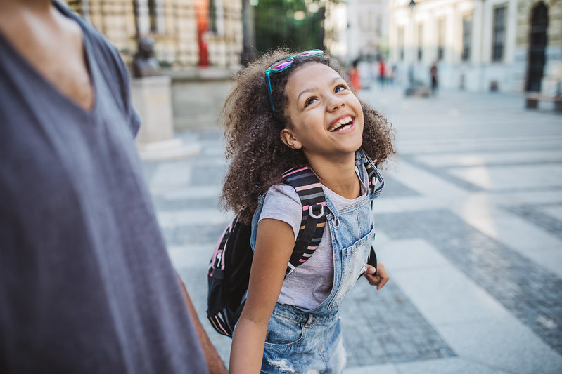 A young girl wearing denim kids' dungarees laughs as she walks with a parent.