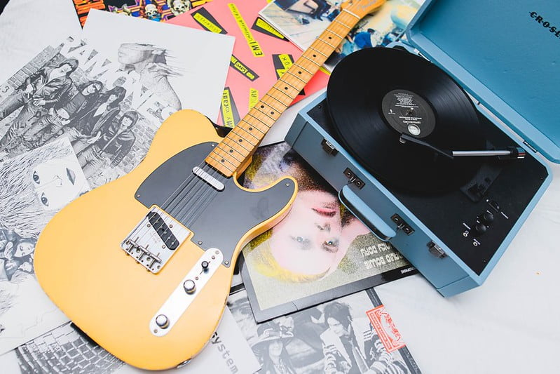 A display of an yellow electric guitar, a record player and some records.