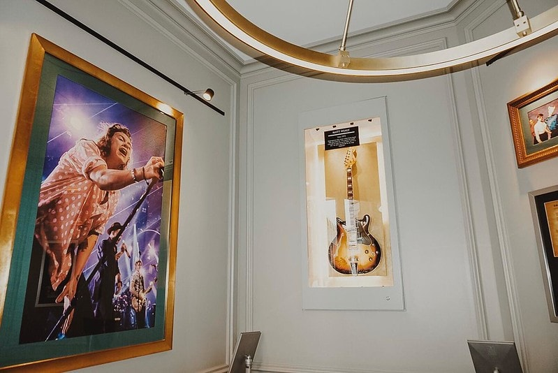 A Harry Styles print and an electric guitar hanging at the Hard Rock Hotel.