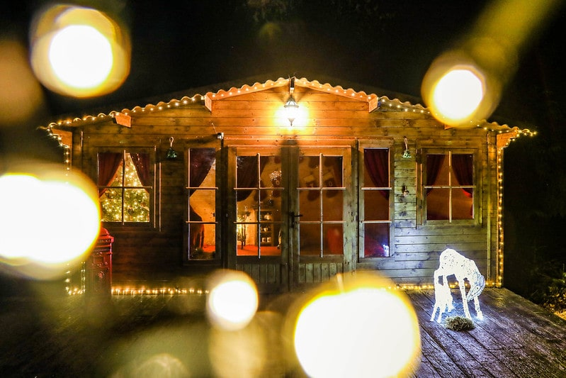 A wooden cabin at Magic of Foresters surrounded by twinkling Christmas lights.