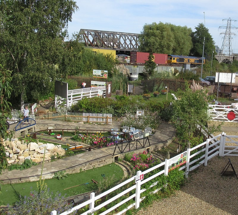 View of miniature railway set, with greenery and wildlife surrounding it.