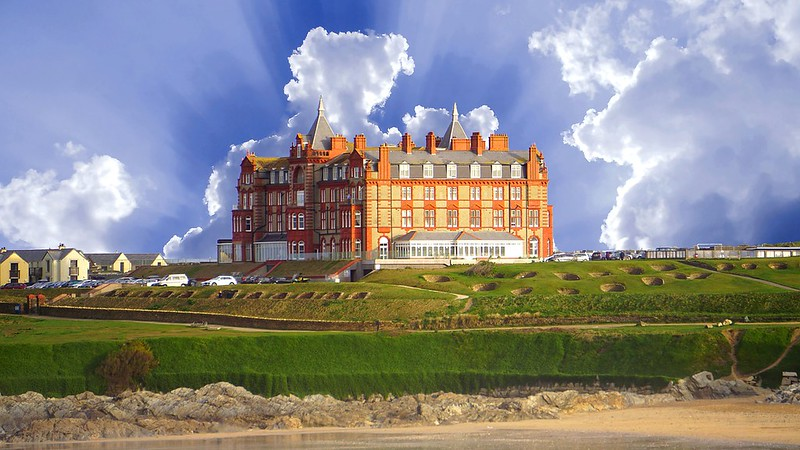 Fistral Beach Hotel from afar on semi cloudy day, green space in front of the grand building.