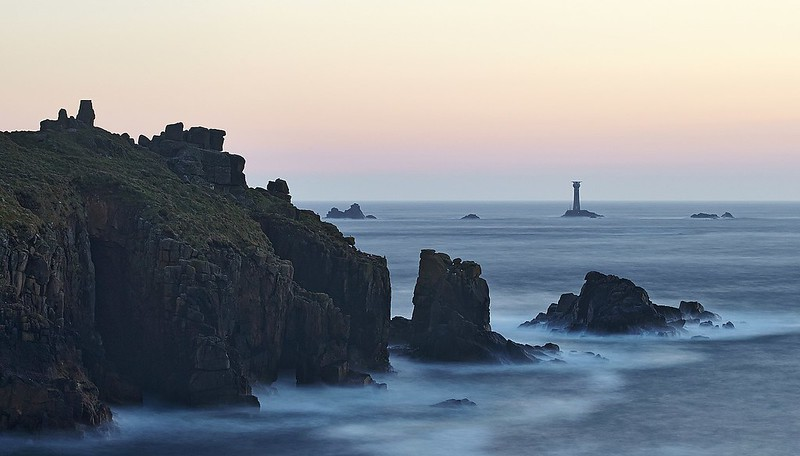 Land's End Longship lighthouse in distance with cliffs as sun sets.