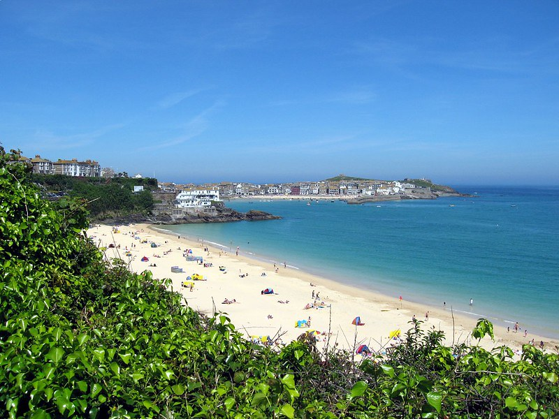 View of Porthminster beach and turquoise seas, overlooked by greenery.