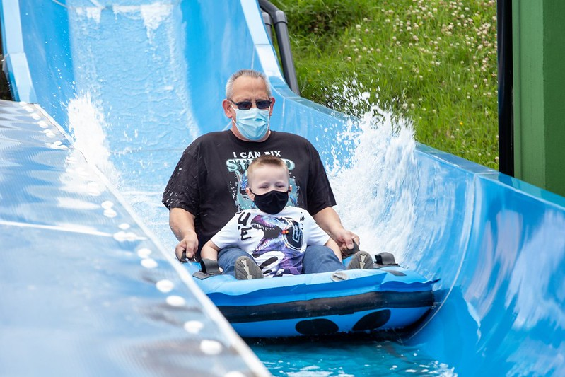 Gulliver's Kingdom blue water slide, dad and child riding down it.