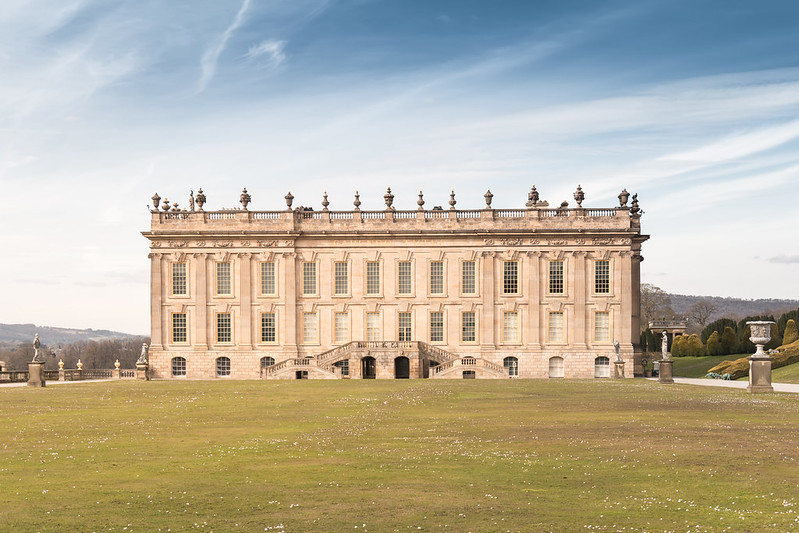 Chatsworth House with green lawn, blue cloudy skies.