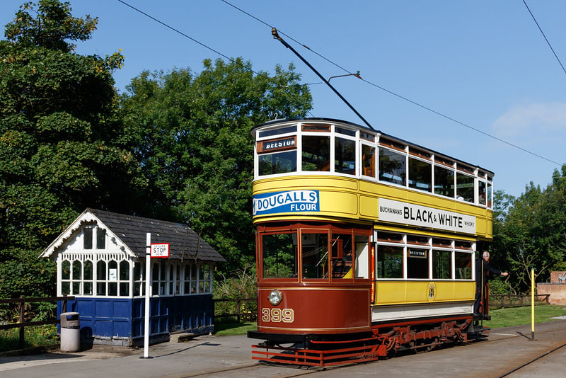 Vintage yellow and red tram and bus stop at Crich Tramway Village.