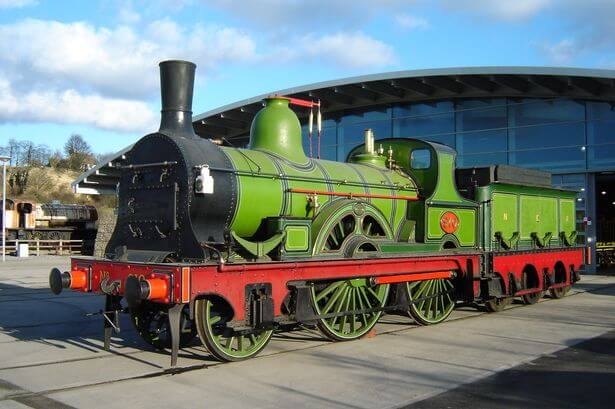 A green steam train outside Locomotion.